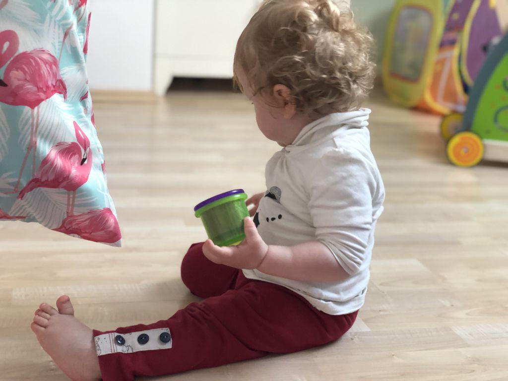Baby spielt mit Stapelbechern